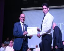 A Merit holder receiving the Certificate of Merit from the Chancellor, AUMP